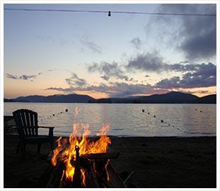 campfire by a lake at dusk