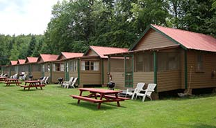 seven cabins with picnic tables in front of each