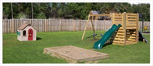 a yard with a sandbox and swingset